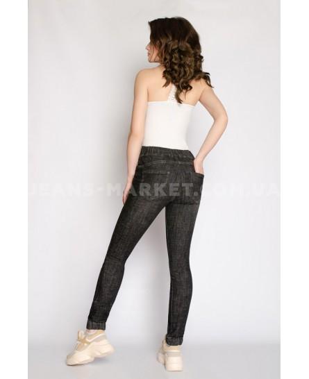 Девушка в модных темных джинсах